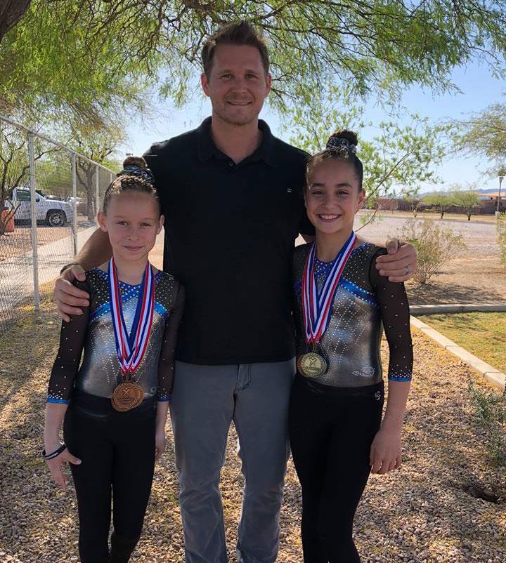 Head gymnastics coach Chris with Kaila and Colleen